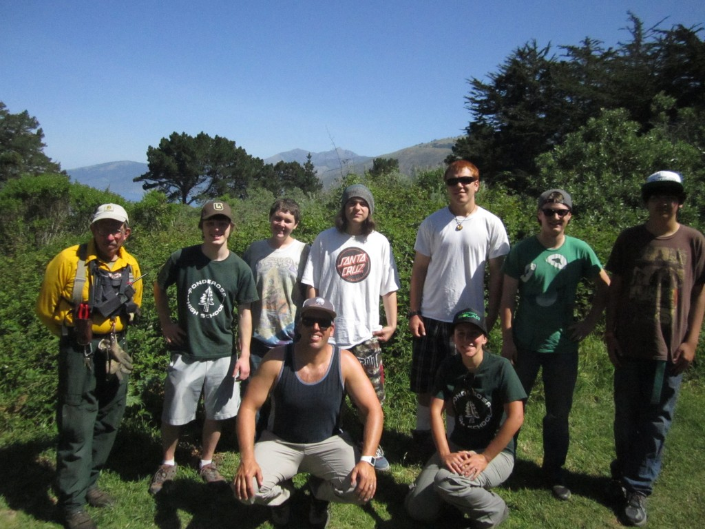 Students and staff of Ponderosa High School pose with Trail Crew leader Mike Heard (left) with Cone Peak in the background