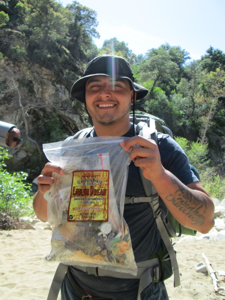 Student Jessie Sanchez holds up a bag of  trash cleaned up at the Arroyo Seco Gorge